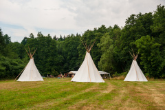 Beautiful view of three tipi tents in a field. Tee pee built on green grass. Traditional teepee tent wigwams located in nature. Czech countryside. Summer wedding.